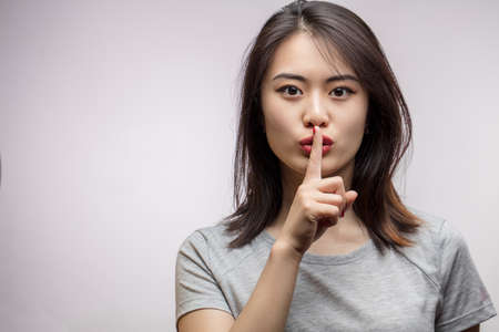 Photo for Asian female model keeping index finger near mouth making hush sign. Closeup portrait of young Korean woman demands silence, respecting woman s secret - Royalty Free Image