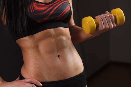 Photo pour Midsection portrait of muscular female body with yellow dumbbell isolated over black background with copyspace. Part of fitness body. Sport and Woman, Bodybuilding Concept - image libre de droit