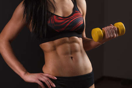 Photo for Midsection portrait of muscular female body with yellow dumbbell isolated over black background with copyspace. Part of fitness body. Sport and Woman, Bodybuilding Concept - Royalty Free Image
