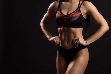 Photo for Sporty sexy female with raised abdominal muscles in black sportswear. Tanned young sexy athletic girl. A great sport female body close up. - Royalty Free Image