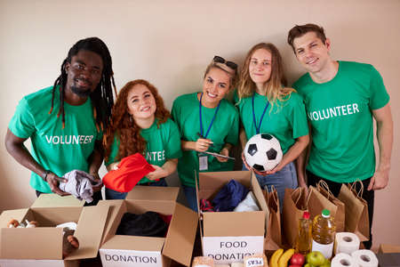 Photo for active young people enjoys volunteering at food and clothes bank, voluntary company. diverse people working in voluntary company with friends putting food for donation into boxes - Royalty Free Image