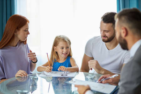 Photo for little caucasian daughter want parents to be together, she is drawing mom and dad on paper, family came to get psychological help and support, what they need to do - Royalty Free Image
