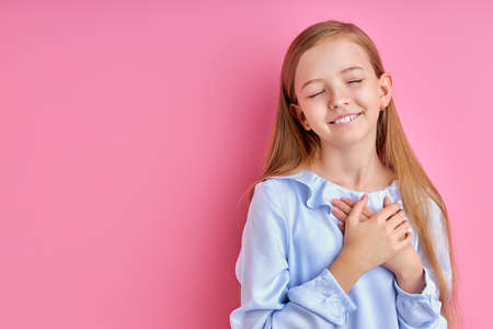 Photo pour kind child girl say thanks or dreaming, holding hands on chest, isolated - image libre de droit