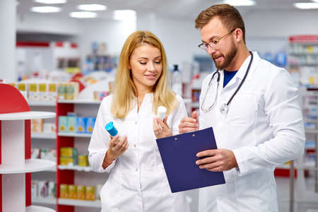 Foto de two young caucasian colleagues in white medical gown pharmacists fulfilling a prescription holding medication in hand, checking the script - Imagen libre de derechos