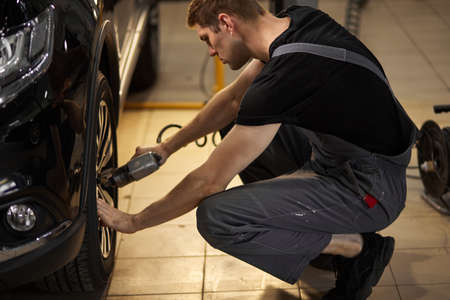 concentrated professional auto mechanic man repairs a wheel that has broken, changing