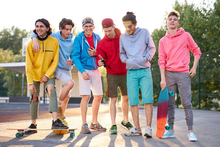 Photo pour portrait of friendly team of sportive teenagers holding basketball ball and skateboard in hands, they are posing at camera, outdoors - image libre de droit