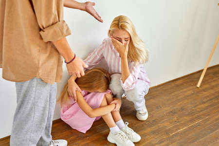 Photo pour blond woman and child girl sits suffering from cruelty of father, abusive relationships concept, man is screaming and punishing members of family - image libre de droit
