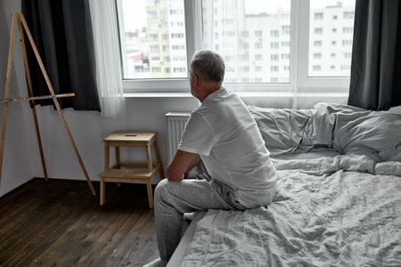 Foto de side view on upset man sitting alone on bed at home in dark room, morning alone. - Imagen libre de derechos