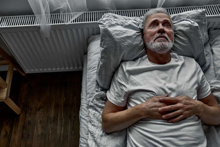 Foto de middle-aged man lying down in bed on pillow, having insomnia sleeping disorder. alone at home - Imagen libre de derechos