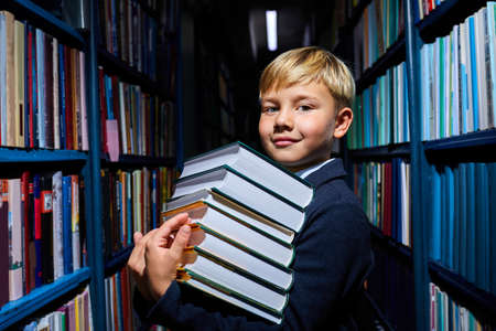 Photo for clever kid boy with stack of books in hands preapring fro school, in library, in school wear - Royalty Free Image