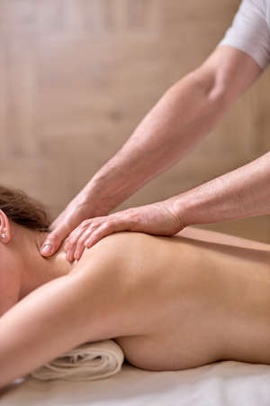 Photo pour Back massage for young female in modern spa salon. Muscle recovery after exercise. Wellness. Back treatment. sports massage. - image libre de droit