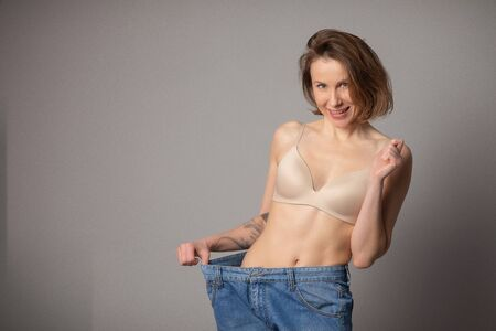 Young Woman Shows her Weight Loss and Wearing Her Old Jeans. Slim Girl in Big Jeans Showing How She Was Losing Weight. Woman with Perfect Fit Body. Weight Loss Concept.