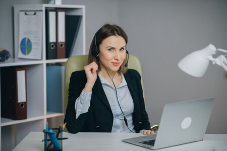 Businesswoman in Headphones Holding Paper Financial Report talk at Webcam make video call in office, business coach looking at camera speak show statistics explain marketing strategy for client.