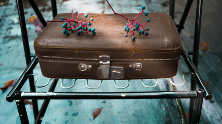 old leather suitcase on a turquoise background