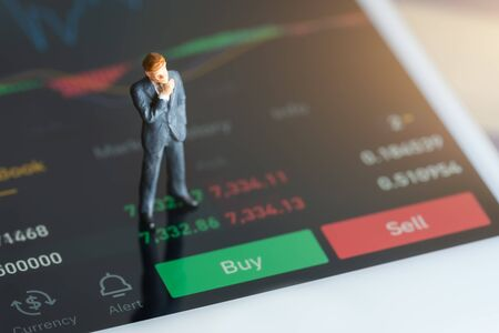 Photo pour Miniature people: Businessman standing on mobile phone, chart, numbers and sell and buy options. red and green candlestick chart and stock trading smartphone screen background. - image libre de droit