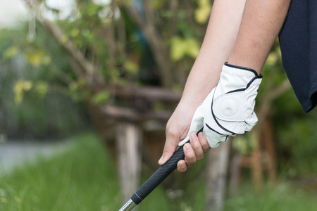 Golfer wearing white glove holdiing golf club two-handed