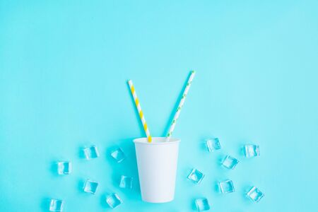 White paper caps with color cocktail straw and ice on blue background. Space for text. recycling eco concept. pop art style. Party
