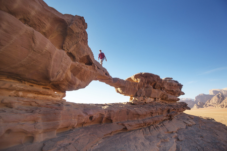 Foto de Tourist on a rock in Wadi Ram desert. Stone bridge arch. Jordan landmark - Imagen libre de derechos