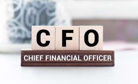 Photo pour CFO Chief Financial Officer written on a wooden cube in front of a laptop. - image libre de droit