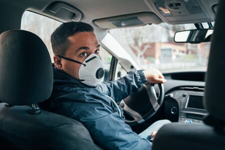 young hispanic man is a driver of the car in a protective mask. prevent the spread of coronavirus. young hispanic taxi driver wearing a protective mask . quarantine.  covid 19. coronavirus.