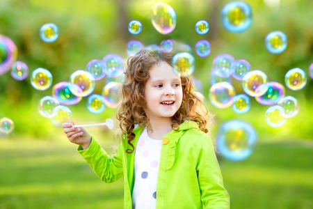 A little girl blowing soap bubbles, spring portrait beautiful curly baby.