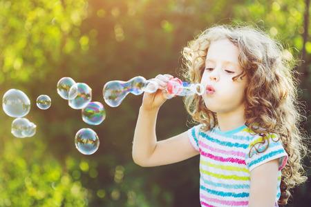 Cute girl blowing soap bubbles, closeup portrait.
