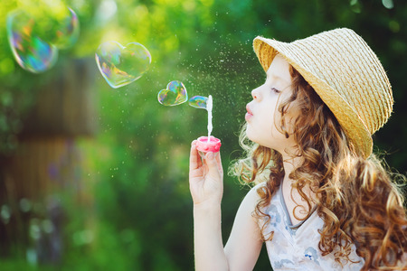 Foto de Lovely little girl blowing soap bubbles in a heart shape. Happy childhood concept.  - Imagen libre de derechos