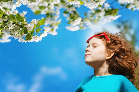 Foto de Little girl closed her eyes and breathes the fresh air in the park. - Imagen libre de derechos