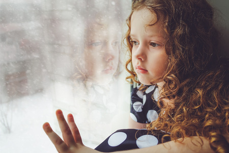 Sad child looking out the window on falling snow. Toning photo.
