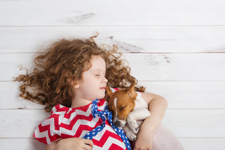 Photo pour Cute girl hugging a puppy and sleeping on warm wooden floor. - image libre de droit