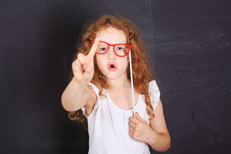 School girl showing shaking finger saying no, near blackboard.