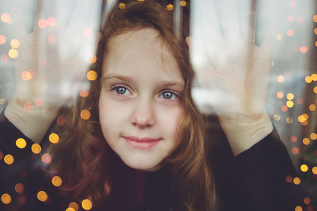 Young girl looking on windows shopping, with illuminated christmas garland. Shopping, black friday sale.