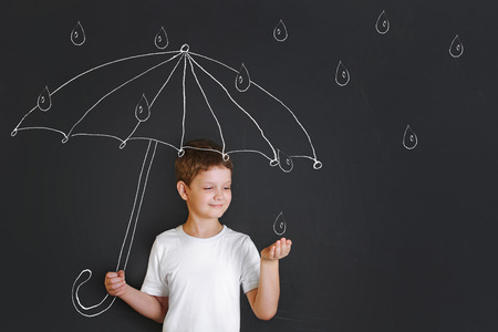 Foto de Handsome boy under chalk drawing umbrella, held out his hand and catches the raindrops. Childhood, fantasy and dreaming concept. - Imagen libre de derechos