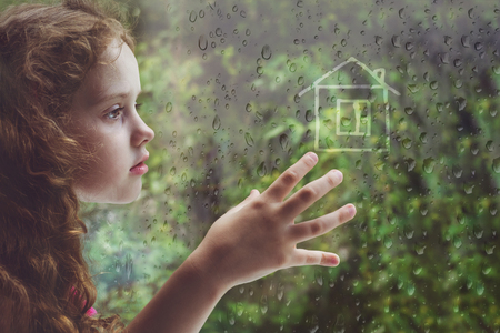 Photo pour Sad curly little girl looking out the rain drop window and draw house. Toning for instagram filter. - image libre de droit