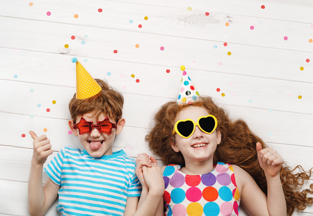 Photo pour Happy children on carnival party, lying on a wooden floor. Happy childhood, Holiday concept. - image libre de droit