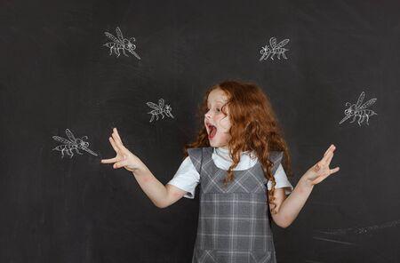 Photo pour Sad little girl afraid of bites mosquitoes flying around her. - image libre de droit