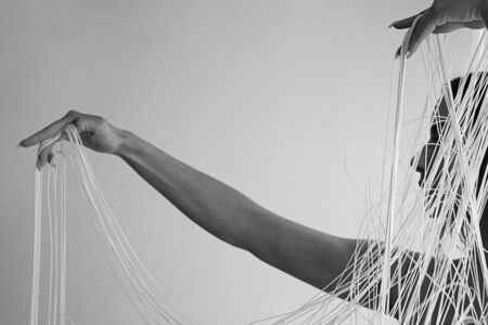 black and white Image of the profile of a young attractive woman with uncovered shoulders, who decoratively draws the white threads of a string curtain with her hands, isolated, copy space