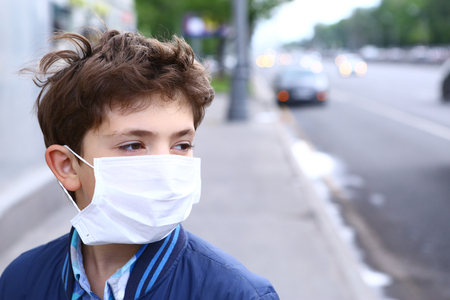 Photo pour preteen boy in protection mask on the highway city background - image libre de droit