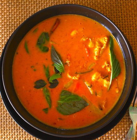 red curry asian thai soup with chicken greens and vegetables close up photo