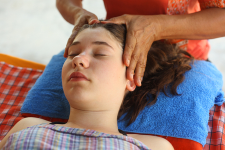 head face thai massage teenager girl with closed eyes and massaging hands close up outdoor photo
