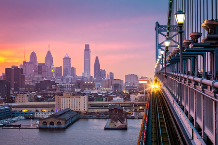 Photo pour Philadelphia under a hazy purple sunset. An incoming train crosses Ben Franklin Bridge. - image libre de droit