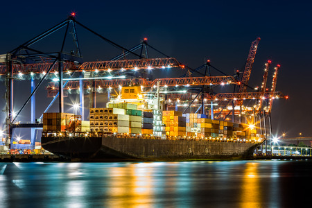 Photo pour Cargo ship loaded in New York container terminal at night viewed from Elizabeth NJ across Elizabethport reach. - image libre de droit