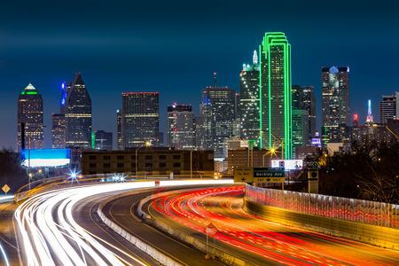 Dallas skyline by night. The rush hour traffic leaves light trails on I30 Tom Landry freeway.