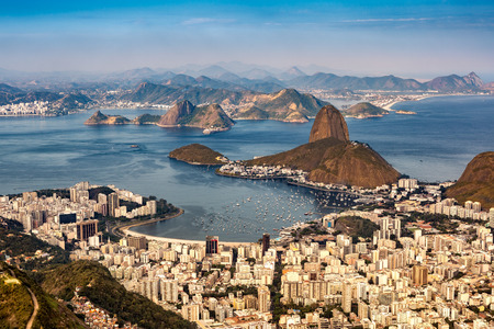 Spectacular aerial view over Rio de Janeiro as viewed from Corcovado. The famous Sugar Loaf mountain sticks out of Guanabara Bay