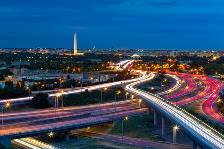 Washington D.C. cityscape at dusk with rush hour traffic trails on I-395 highway. Washington Monument, illuminated, dominates the skyline.
