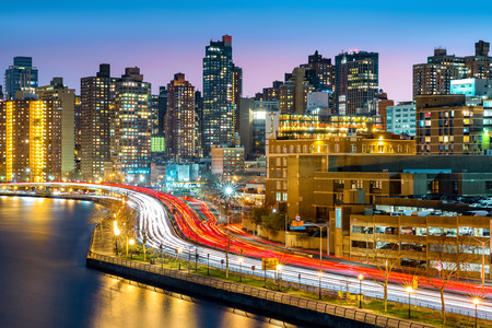 East Harlem neighborhood skyline with rush hour traffic on FDR drive, at dusk, in Manhattan, New York City