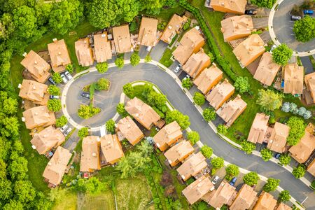 Photo pour Late afternoon, birds eye view of a suburban community in New Jersey. Row of houses align along winding roads - image libre de droit