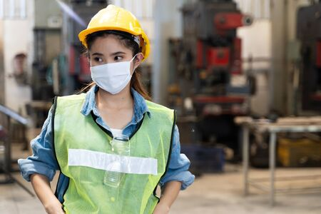 Photo for Asian women worker factory wearing mask protection face for safety stands in machine industrial factory. - Royalty Free Image