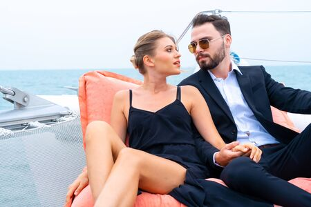 Photo pour luxury relaxing couple traveler in nice dress and suite sit on bean bag in part of cruise yacht with background of sea and white sky. Concept business travel. - image libre de droit