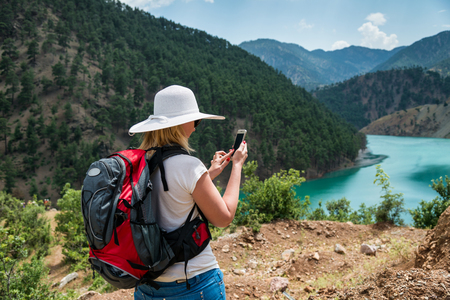 Woman backpacker using smart phone in mountains